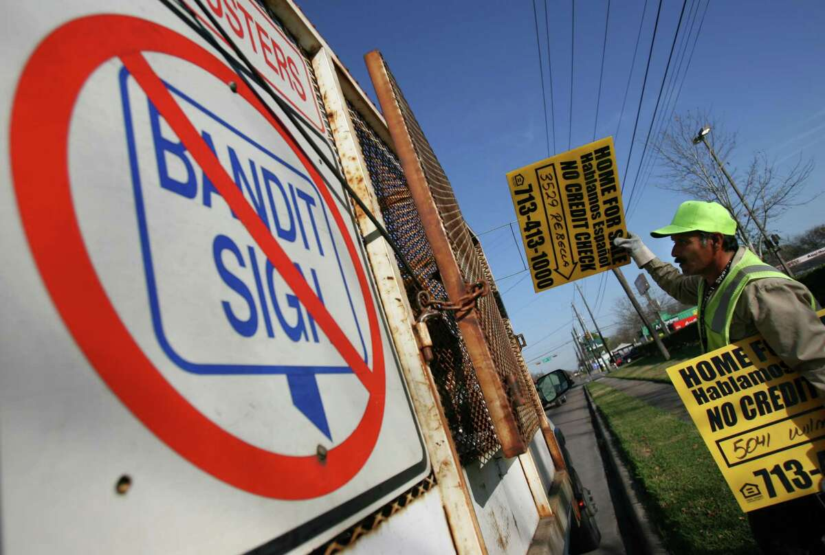 Nicolas Cortez (cq), a city of Houston Public Works employee collects bandit signs along Reed Road on Wednesday January 9, 2008 in Houston. City workers routinely collect the signs from publicly owned sections. (Chronicle) Sharon Steinmann