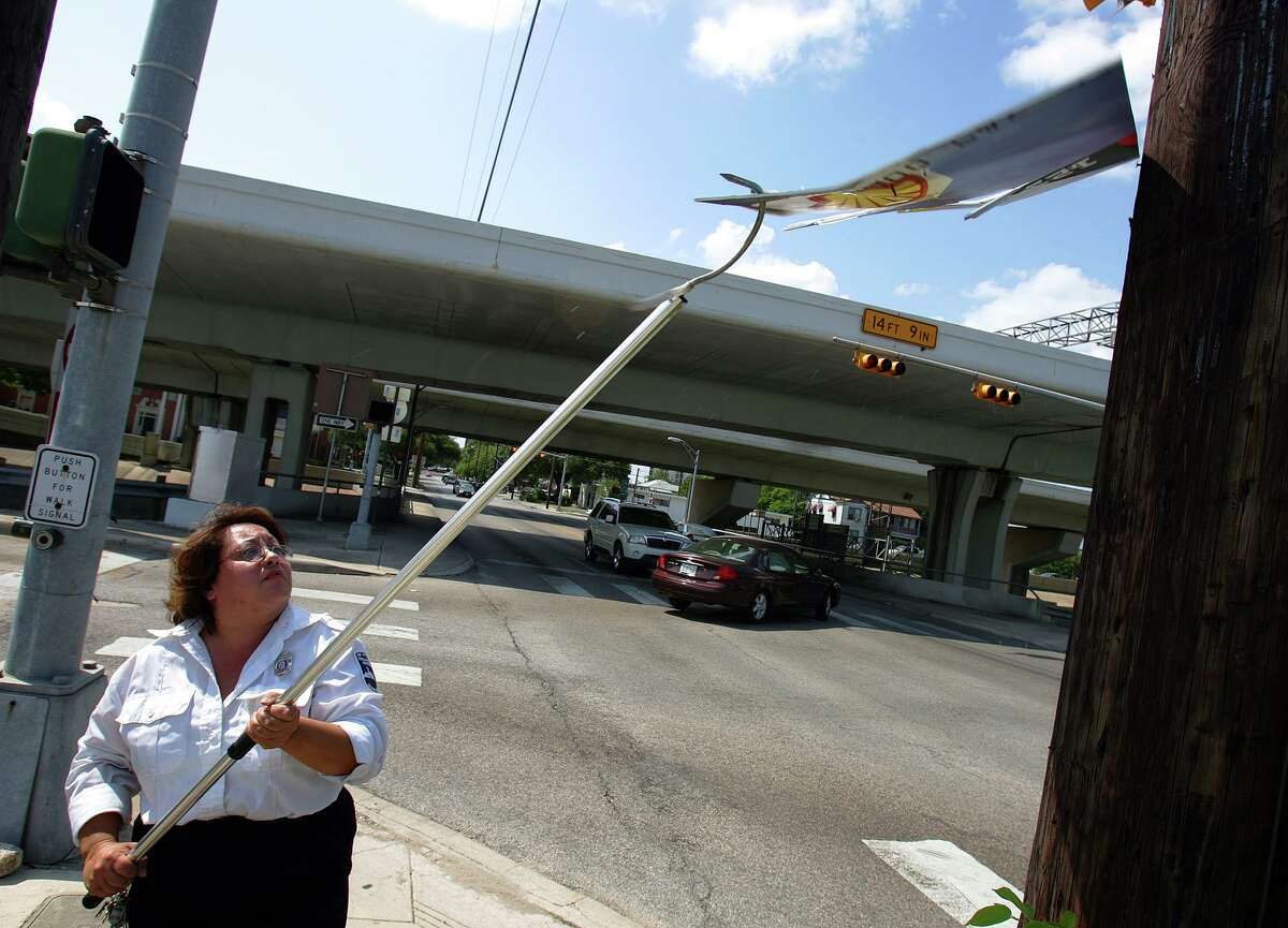 City Sign Inspector Arlene Rodriguez takes up bandit signs Wednesday June 8, 2005 on McCullough Street downtown. BAHRAM MARK SOBHANI/STAFF
