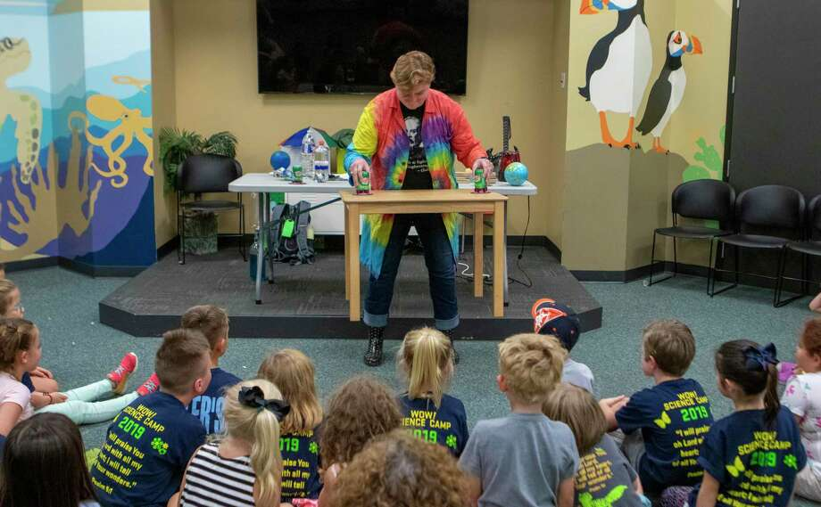 Science teacher and former camper Kasey Fowler lifts a table with soda cans and suction cups to demonstrate air pressure to children Thursday, June 11, 2019 during Wonders of The Woodlands Science Camp at The Woodlands United Methodist Church. Photo: Cody Bahn, Houston Chronicle / Staff Photographer / © 2019 Houston Chronicle