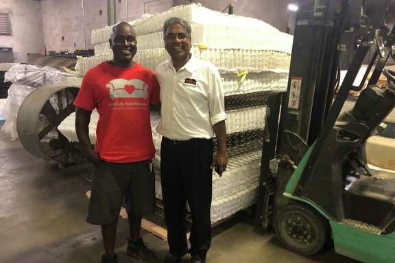 Carye Blackwood, manager of mattress recycling at the Houston Furniture Bank (pictured left), and Executive Director Oli Mohammed pose in front of some mattresses in the process.