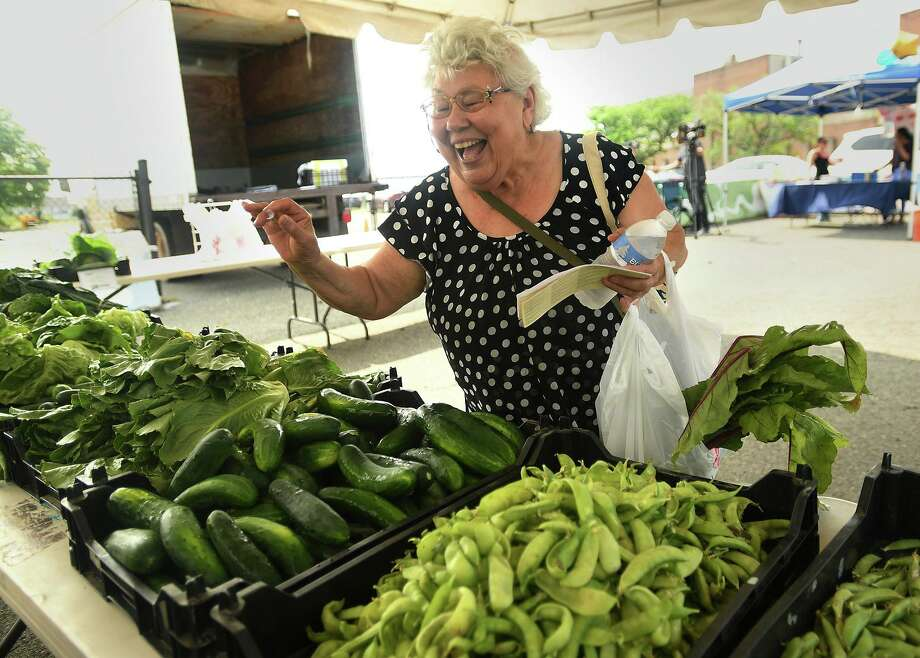 Margarita Montalvo, of Bridgeport, picks out fresh vegetables during the opening day of the East Side Farm Market on East Main Street in Bridgeport, Conn. on Wednesday, July 10, 2018. The Bridgeport Farmers Market Collaborative features eight independently-operated markets in different sections of the city. Photo: Brian A. Pounds / Hearst Connecticut Media / Connecticut Post