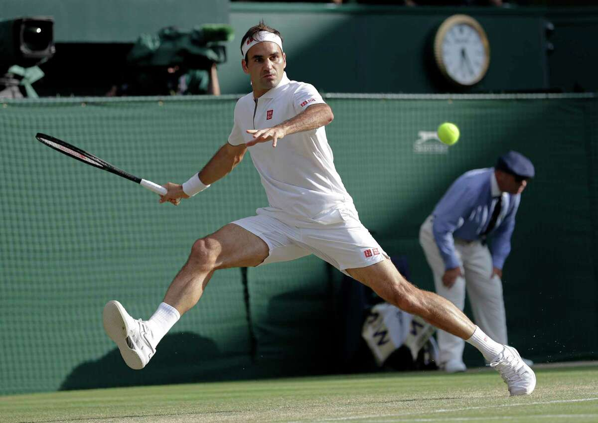 Switzerland's Roger Federer returns the ball to Spain's Rafael Nadal during a men's singles semifinal match on day eleven of the Wimbledon Tennis Championships in London, Friday, July 12, 2019.