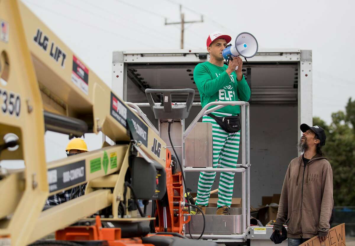 Encampment resident Oz (right) confronts Oakland landlord Gene Gorelik as he stands on a boom lift with a megaphone during a demonstration held at a homeless encampment along Alameda Avenue behind Home Depot in Oakland, Calif. Friday, July 12, 2019. Gorelik, a real estate developer previously sued by the city, rented the boom lift to offered money to residents of a homeless encampment if they leave.
