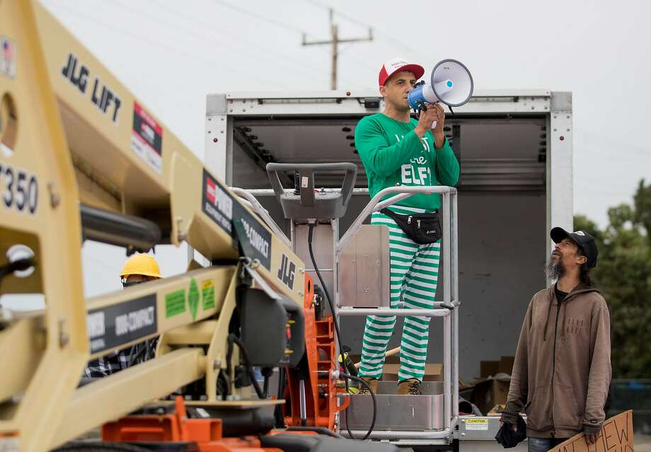 Encampment resident Oz (right) confronts Oakland landlord Gene Gorelik as he stands on a boom lift with a megaphone during a demonstration held at a homeless encampment along Alameda Avenue behind Home Depot in Oakland, Calif. Friday, July 12, 2019. Gorelik, a real estate developer previously sued by the city, rented the boom lift to offered money to residents of a homeless encampment if they leave. Photo: Jessica Christian / The Chronicle