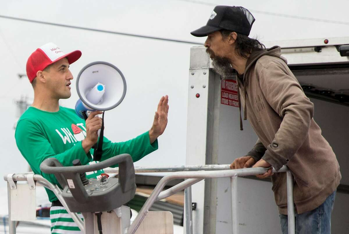 Homeless encampment resident Oz (right) confronts Oakland landlord Gene Gorelik as he stands on a boom lift with a megaphone during a demonstration held at a homeless encampment along Alameda Avenue behind Home Depot in Oakland, Calif. Friday, July 12, 2019. Gorelik, a real estate developer previously sued by the city, rented the boom lift to offered money to residents of a homeless encampment if they leave.