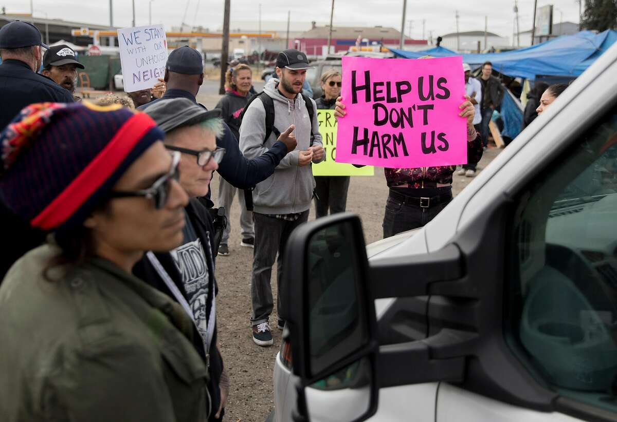 Homeless advocates block Gene Gorelik from driving his rented truck during a protest held at a homeless encampment along Alameda Avenue behind Home Depot in Oakland, Calif. Friday, July 12, 2019. Gorelik, a real estate developer previously sued by the city, entered the encampment with a rented boom lift to offer money to residents if they leave.