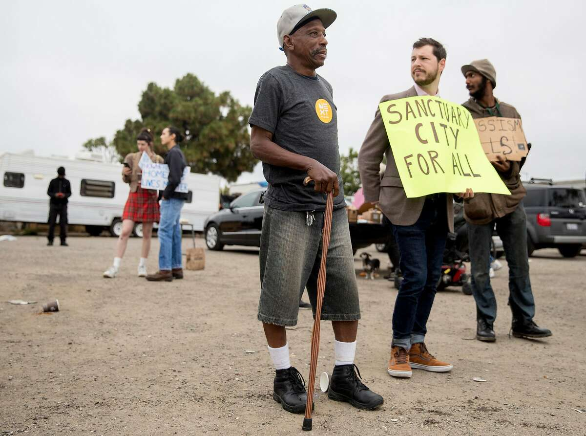 Encampment resident Curtis James stands with advocates during a protest held at a homeless encampment behind Home Depot in Oakland, Calif. Friday, July 12, 2019. Gene Gorelik, a real estate developer previously sued by the city, held a large demonstration, rented a boom lift and offered money to residents of a homeless encampment if they leave.