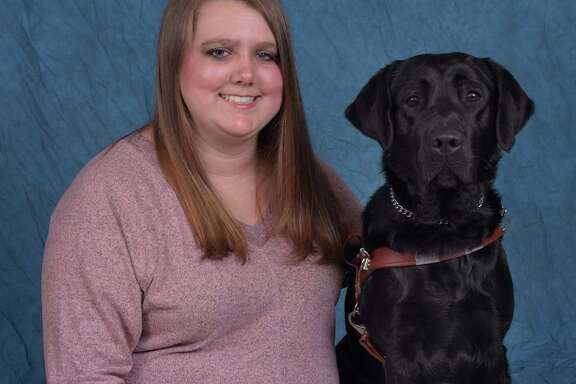Cypress native Ashley Pryor sits with her new guide dog from Guiding Eyes for the Blind, Yaz.