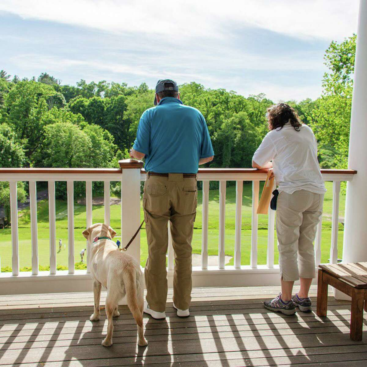 Volunteers Frank Pennacchio and Karin Horowitz along with yellow Labrador retriever guide dog Jiffy watch the golfing action from the porch overlooking the golf course.