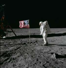 (20 July 1969) --- Astronaut Edwin E. Aldrin Jr., lunar module pilot of the first lunar landing mission, poses for a photograph beside the deployed United States flag during an Apollo 11 extravehicular activity (EVA) on the lunar surface. The Lunar Module (LM) is on the left, and the footprints of the astronauts are clearly visible in the soil of the moon. Astronaut Neil A. Armstrong, commander, took this picture with a 70mm Hasselblad lunar surface camera.