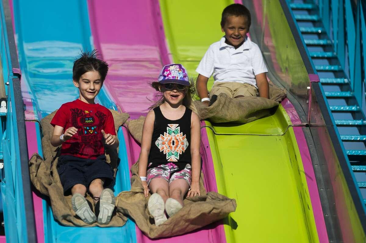 Children slide down the big slide at the Auburn Cornfest on Thursday, July 11, 2019 in Auburn. (Katy Kildee/kkildee@mdn.net)