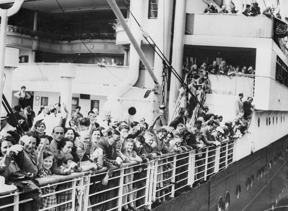 A crowd of German-Jewish refugees aboard the MS St. Louis ocean liner wave as they arrive in Antwerp, Belgium, after wandering the Atlantic for thousands of miles. The boat was denied entry when it reached the port of Havana, Cuba, even though passengers held documents permitting them to enter the country.