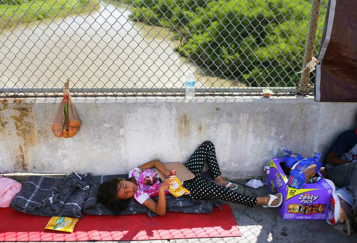 Seven-year-old Yenci Bindel Rodriguez, from Honduras, lays where she has been waiting for the past three nights on the Mexican side of the middle of the Brownsville & Matamoros Express International Bridge for the fourth day in a row hoping for his family to be able to pass together into the United States to seek asylum, Wednesday, June 27, 2018 in Brownsville. Yenci, along with her parents and three siblings, are hoping to escape violence threats against the family in their hometown in Honduras. ( Mark Mulligan / Houston Chronicle )