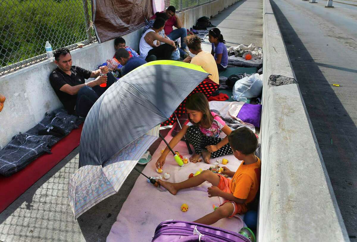 Five-year-old Jesus Bindel Rodriguez and his sister, Yenci Vindel Rodriguez, both from Honduras, play together where they have been waiting for the past three nights on the Mexican side of the middle of the Brownsville & Matamoros Express International Bridge for the fourth day in a row hoping for his family to be able to pass together into the United States to seek asylum, Wednesday, June 27, 2018 in Brownsville. The kids, along with his parents and two more siblings, are hoping to escape violence threats against the family in their hometown in Honduras. ( Mark Mulligan / Houston Chronicle )