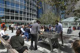 Sherry Siddiqi (middle left))  and Deloitte Prateek Malik (right) take a break for lunch at Salesforce Park playing foosball on Thursday, July 11, 2019 in San Francisco, Calif.