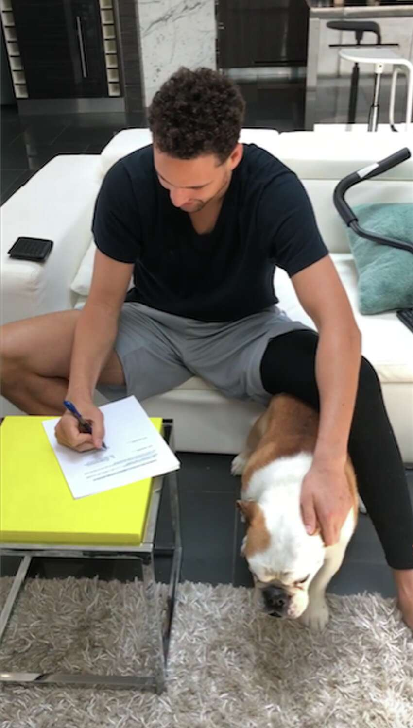 Klay Thompson signs his new Warriors contract with his bet bulldog Rocco.