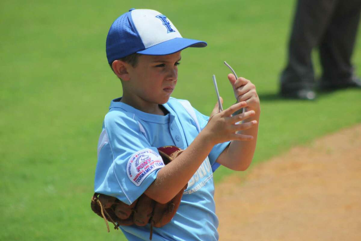 Third baseman Carter Hunter gets ready to put his sunglasses back on before the Elgin All-Stars came to bat during Friday afternoon's game.