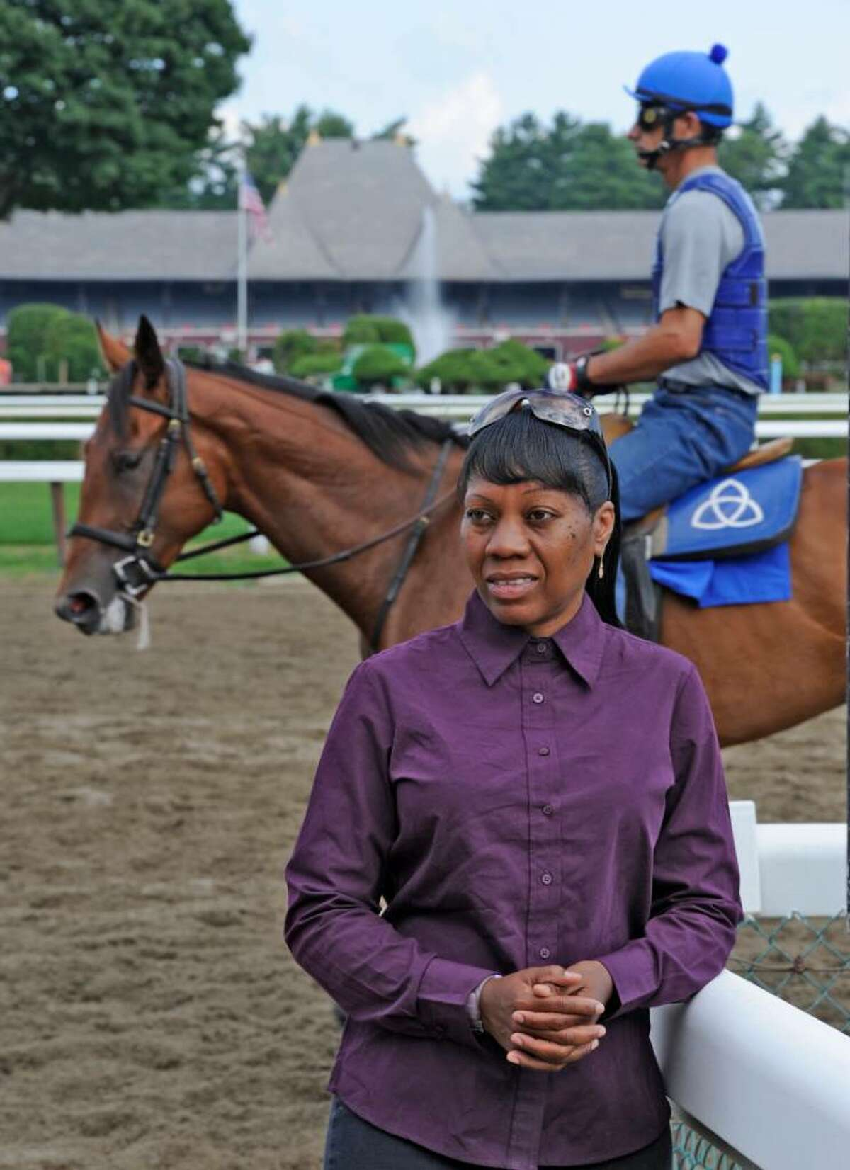 Saudi Burton, a gap attendant at the Saratoga Race Course, stands near Barn 22. She's been trying to get a job with Sheikh Mohammed bin Rashid Al Maktoum, a thoroughbred horse owner who is also the ruler of Dubai and vice president and prime minister of the United Arab Emirates. (Skip Dickstein/Times Union)
