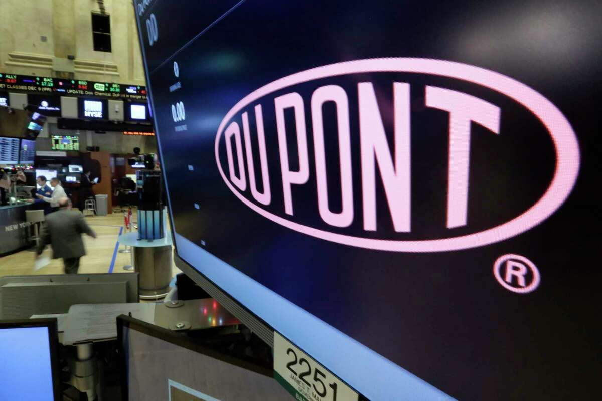 FILE - In this Dec. 9, 2015, file photo, the company name of Dupont appears above its trading post on the floor of the New York Stock Exchange. Chemical manufacturer Chemours says the DuPont Co. massively downplayed the cost of environmental liabilities that Chemours would be saddled after it was spun off from DuPont in 2015. A lawsuit unsealed Friday, June 28, 2019 says the maximum liability exposure figures that DuPont certified prior to the spinoff have proven to be a€œsystematically and spectacularly wrong.a€ DuPont has filed a motion to dismiss the lawsuit, saying any disputes arising from the spinoff must be resolved through private arbitration. (AP Photo/Richard Drew, File)
