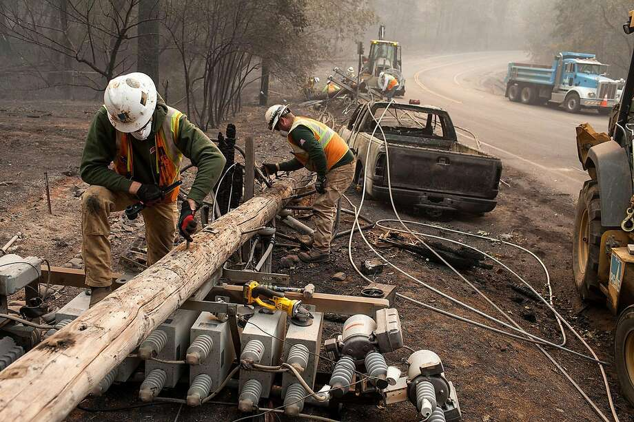 PG&E workers disassemble broken power lines after the Camp Fire ripped through Paradise (Butte County) in November. A new state fund would reimburse utilities for settlements to wildfire victims. Photo: Joel Angel Juarez / Zuma Press 2018
