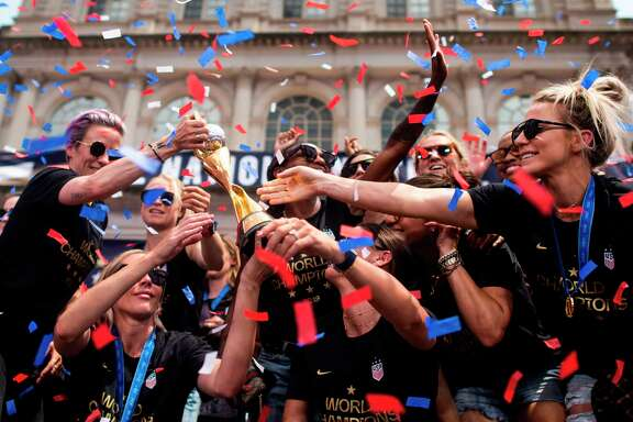 "Members of the World Cup-winning US women's team take part in a ticker tape parade with their trophy for the women's World Cup champions on July 10, 2019 in New York. - Tens of thousands of fans are poised to pack the streets of New York on Wednesday to salute the World Cup-winning US women's team in a ticker-tape parade. Four years after roaring fans lined the route of Lower Manhattan's fabled ""Canyon of Heroes"" to cheer the US women winning the 2015 World Cup, the Big Apple is poised for another raucous celebration. (Photo by Johannes EISELE / AFP)JOHANNES EISELE/AFP/Getty Images"