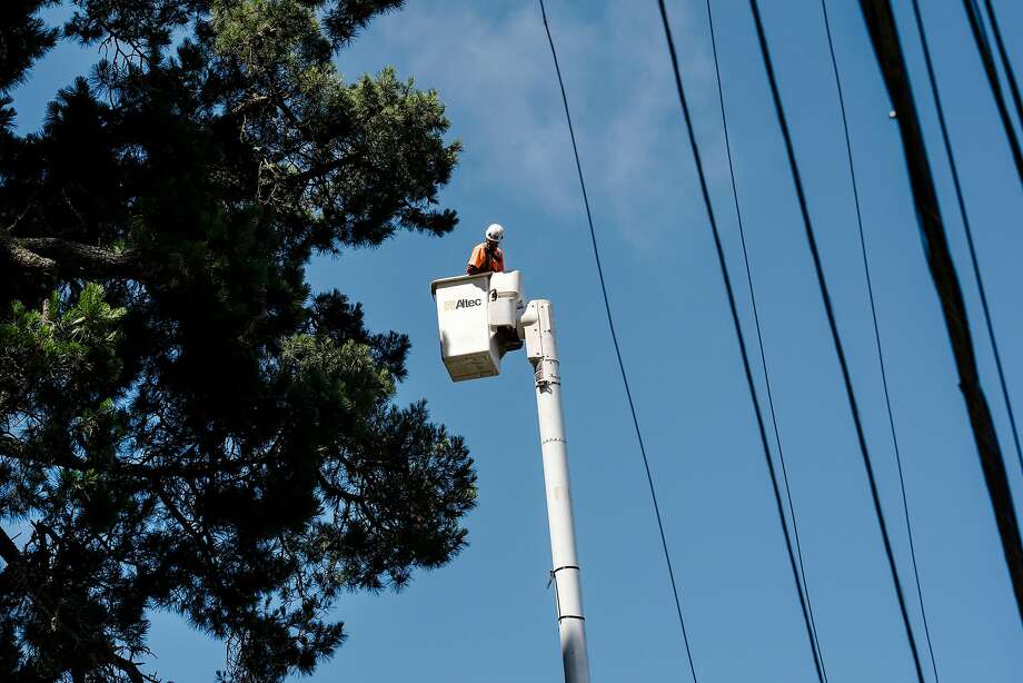 Jose Villeda with Mowbray's Tree Service, contracted by PG&E to handle vegetation management, rides in a cherry picker up to a tree he is preparing to trim back along Skyline Blvd. in Oakland, CA on June 26th, 2019. Photo: Michael Short, Special To The Chronicle