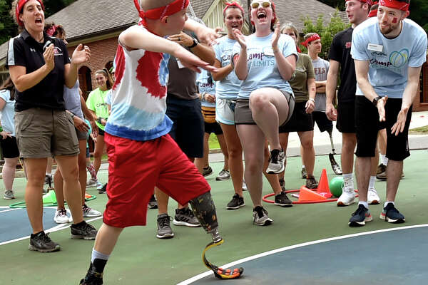 """Hamden, Connecticut -Friday, July 12, 2019: Ryan Werner, 9, of Syracuse, NY dances at Camp No Limits hosted by Quinnipiac University's occupational and physical therapy programs, an overnight camp for children and adolescents with limb loss and their families Friday during a """"Color Wars"""" field day program competition at its York Hill Campus in Hamden. The camp runs through July 14. Camp No Limits purpose is to increase the functional independence of children living with limb loss. Approximately 22 campers and their families will participate in adaptive recreational activities,life skills programs and learn about the latest innovations in prosthetic options. These events will be led by physical and occupational therapists, prosthetists, Quinnipiac students and faculty, and teen and adult amputee mentors. Sports at the camp will include volleyball, sled hockey, basketball and bike clinics. Quinnipiac University is the first and only institution of higher education in the country to host Camp No Limits. Camp No Limits was founded in 2004 by Mary Leighton, an occupational therapist from Maine. The camp began with four children. Today, there are ten locations nationwide, serving hundreds of families. In addition to Connecticut, Camp No Limits is offered in California, Florida, Idaho, Maine, Maryland, Missouri and Texas."""