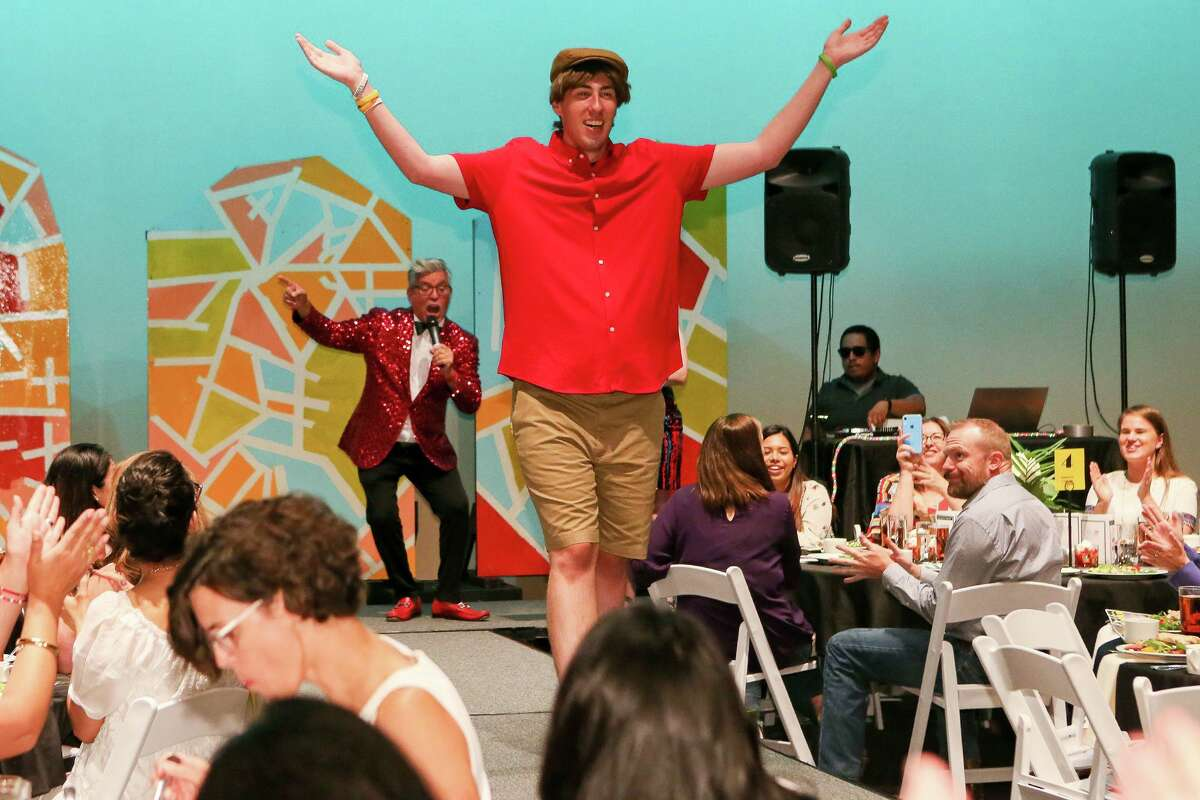 Master of Ceremonies Michael Quintanilla (rear) describes Casey on the runway wearing a Murano red shirt, Roundtree & Yorke shorts featuring a flat front and sporting a brown straw driving cap on the runway in Eva's Heroes Fashion Show, a fashion show produced by and starring teens and adults with intellectual special needs at the Palo Alto College Performing Arts Center on Friday, July 12, 2019.
