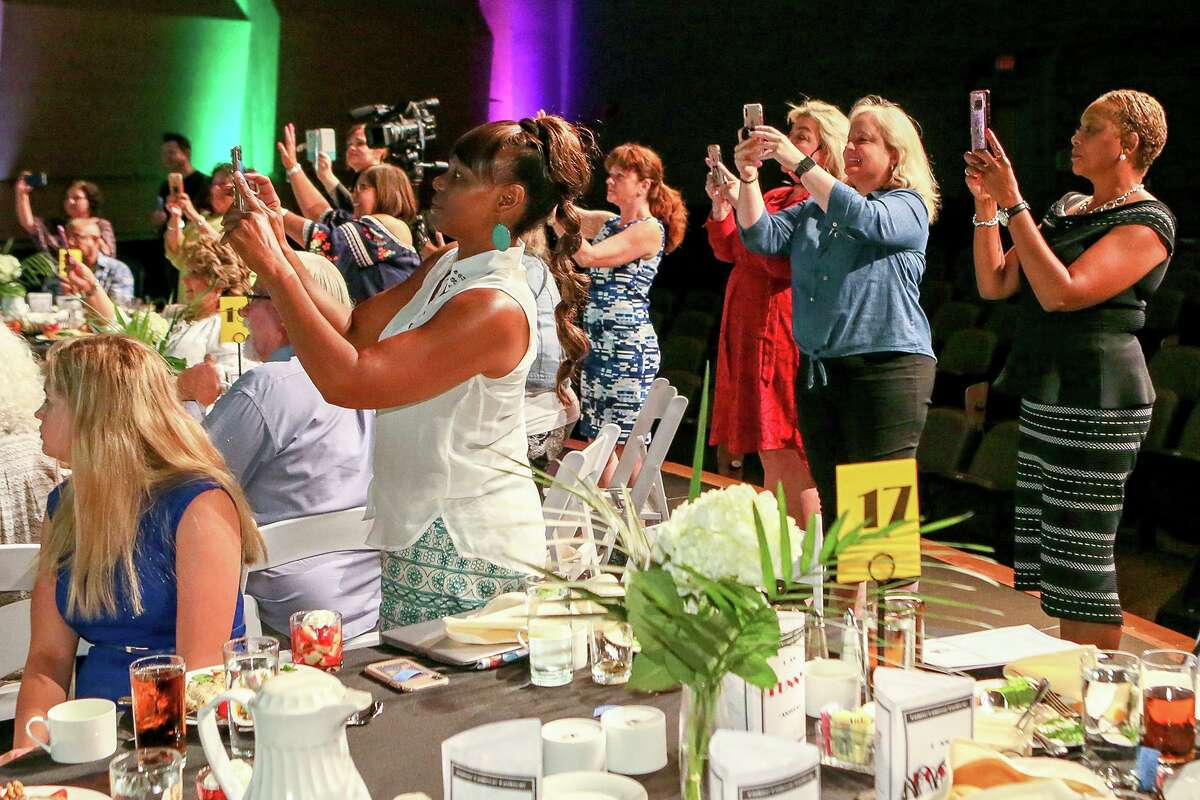 Members of the audience record the grand finale on stage during Eva's Heroes Fashion Show, a fashion show produced by and starring teens and adults with intellectual special needs at the Palo Alto College Performing Arts Center on Friday, July 12, 2019.
