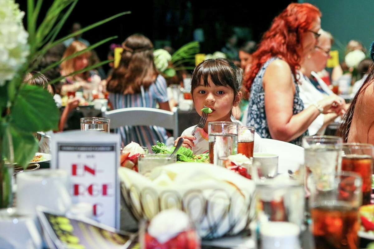 A young girl eats her salad as Eva's Heroes Fashion Show, a fashion show produced by and starring teens and adults with intellectual special needs, gets underway at the Palo Alto College Performing Arts Center, where the audience ejoyed lunch during the show on Friday, July 12, 2019.