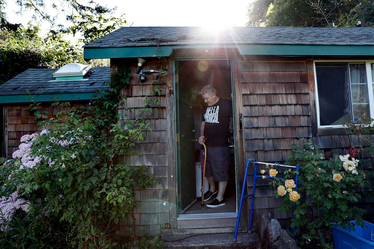 Glenn Sauber transfers to a walker to go back to his house from his band practice room at his home in Sebastopol, Calif., on Wednesday, July 10, 2019.