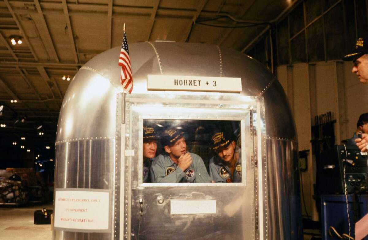 Apollo 11 astronauts Edwin Aldrin, Jr., left, Neil Armstrong, and Michael Collins are seen in quarantine in the Mobile Quarantine Facility as they are transported from the Pacific Ocean to Johnson Space Center in Houston.
