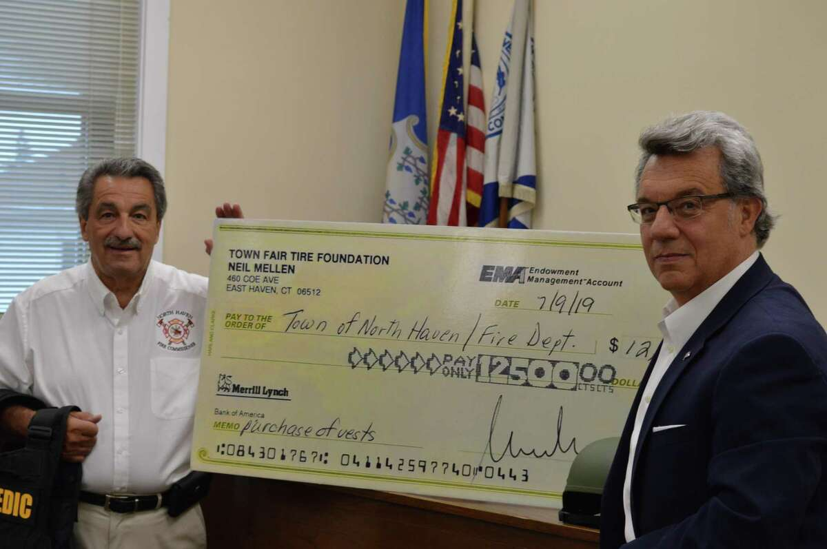 North Haven Fire Commission Chairman Peter Criscuolo, left, and Town Fair Tire Foundation member Dan Rubino, right, standing with a $12,500 check from the Town Fair Tire Foundation given to the Fire Department to buy 10 ballistic vests and helmets.