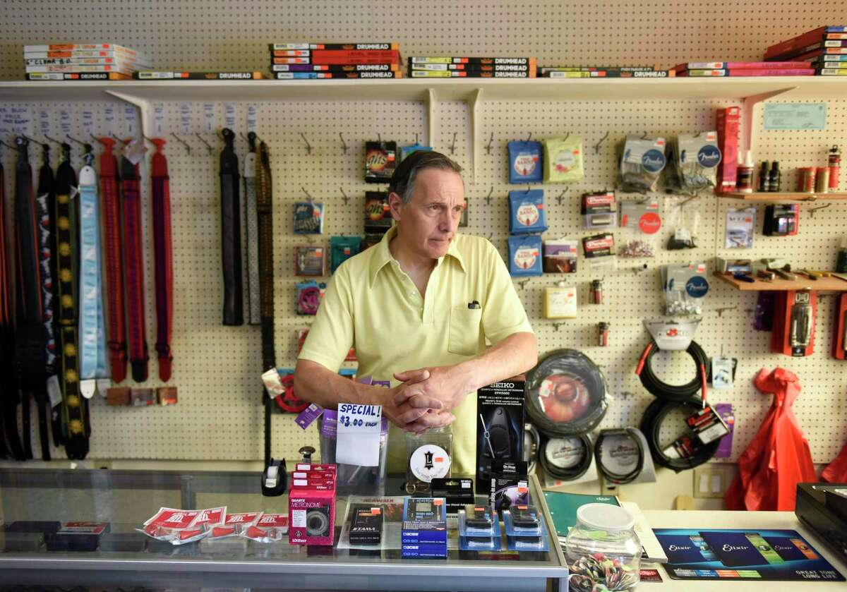Store owner Joe Roberts tells a story at the counter of Connecticut Music in Stamford, Conn. Thursday, July 11, 2019. Roberts' brother, Mike, passed away on New Years Eve and Joe has been running the business by himself since then. After 70 years in business, the store will close its doors this month, but Roberts will still be available for instrument repairs out of his home.