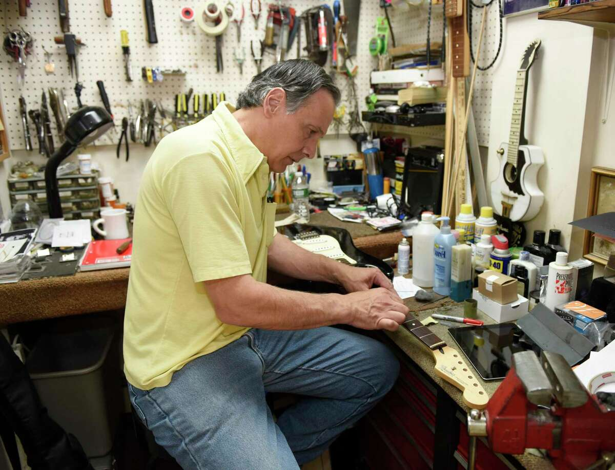 Store owner Joe Roberts repairs a guitar at Connecticut Music in Stamford, Conn. Thursday, July 11, 2019. Roberts' brother, Mike, passed away on New Years Eve and Joe has been running the business by himself since then. After 70 years in business, the store will close its doors this month, but Roberts will still be available for instrument repairs out of his home.