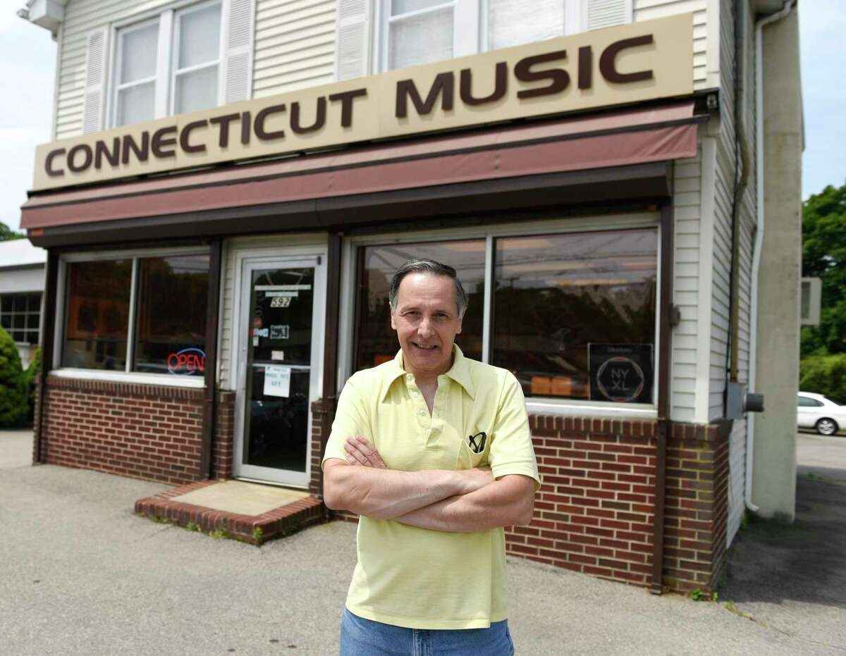 Store owner Joe Roberts poses outside Connecticut Music in Stamford, Conn. Thursday, July 11, 2019. Roberts' brother, Mike, passed away on New Years Eve and Joe has been running the business by himself since then. After 70 years in business, the store will close its doors this month, but Roberts will still be available for instrument repairs out of his home.