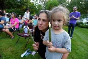 Massiel Zucco-Himmelstein of Stamford and her daughter Ava Himmelstein participate in a candle lighting ceremony during a Lights for Liberty vigil at the North Stamford Community Church in North Stamford on Friday.