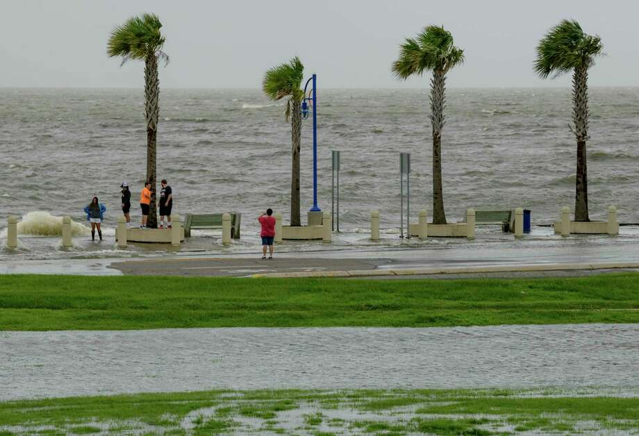 People check out the waves on Lakeshore Drive in New Orleans, La., Friday, July 12, 2019, as water moves in from Lake Pontchartrain from the storm surge from Tropical Storm Barry in the Gulf of Mexico. The area is behind a levee that protects the rest of the city. (AP Photo/Matthew Hinton) Photo: Matthew Hinton / FR 170690AP