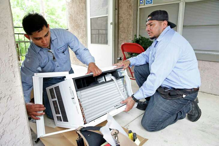 Christopher Ramon, left, and Rene Yanez with Premier Comfort A/C & Heating prepare one of the 12,000 BTU air conditioners as SAHA installs new AC units at the Pin Oak I apartments, a public housing complex which serves seniors and disabled citizens on May 7, 2019.
