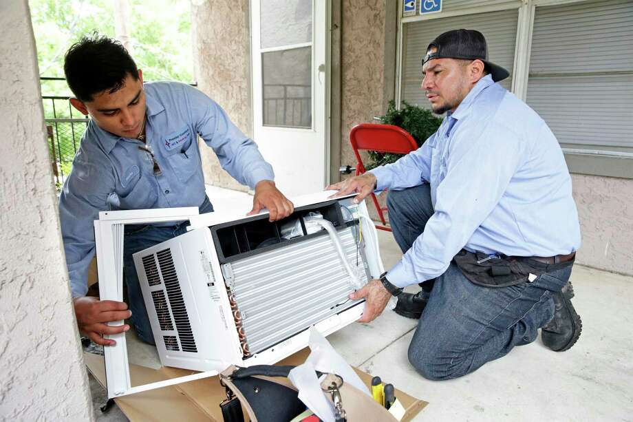 Christopher Ramon, left, and Rene Yanez with Premier Comfort A/C & Heating prepare one of the 12,000 BTU air conditioners as SAHA installs new AC units at the Pin Oak I apartments, a public housing complex which serves seniors and disabled citizens on May 7, 2019. Photo: Tom Reel, Staff / Staff Photographer / 2019 SAN ANTONIO EXPRESS-NEWS