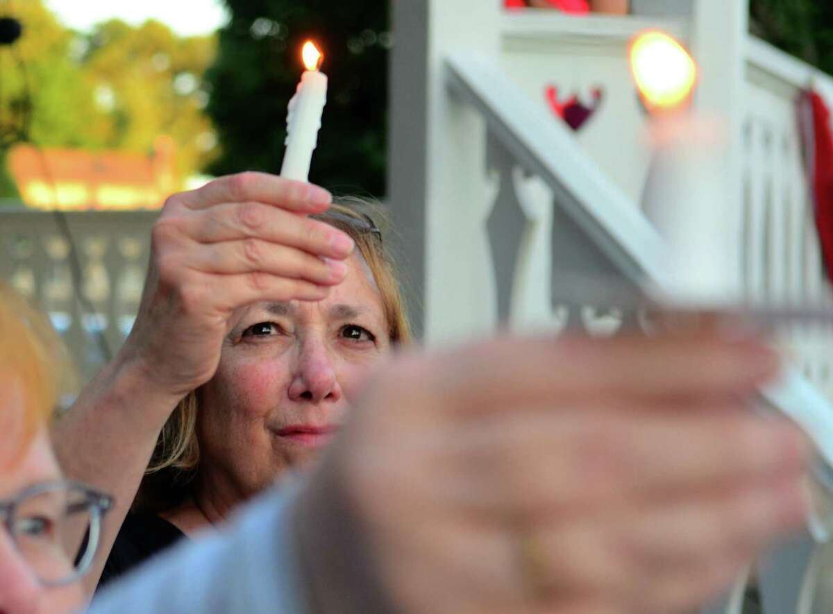 Fairfield resident Kathy Lotty holds a candle during the Lights for Liberty vigil in Fairfield on Friday.
