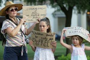 Caroline Atwood, left, and her daughters Catherine, center, and Elisabeth hold up signs they fashioned on plain paper for the Lights for Liberty event at Travis Park on July 12, 2019.