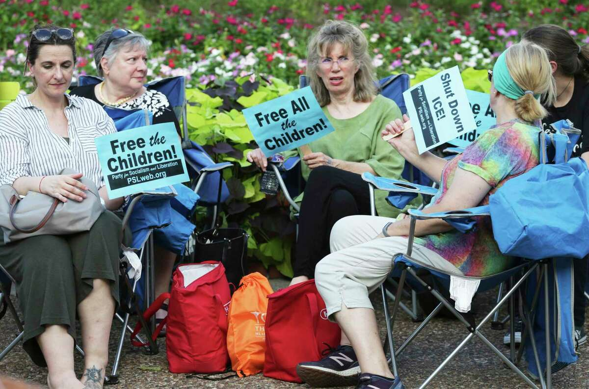 Signs are used as fans to beat the stifling late afternoon heat during the Lights for Liberty event at Travis Park on July 12, 2019.