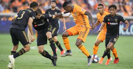 Houston Dynamo forward Romell Quioto (31) battles Los Angeles FC defenders to keep control of the ball during the first half of an MLS soccer match Friday, July 12, 2019, in Houston.