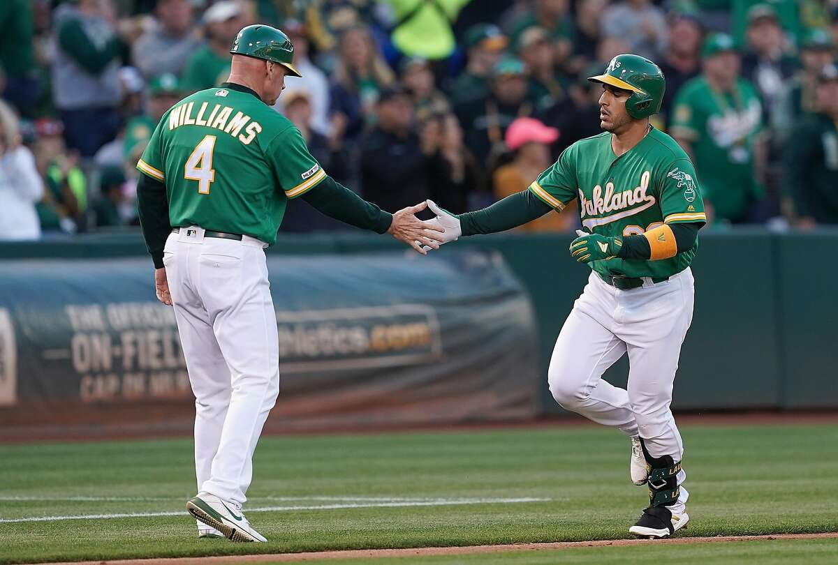OAKLAND, CA - JULY 12: Ramon Laureano #22 of the Oakland Athletics is congratulated by third base coach Matt Williams #4 after Laureano hit a solo home run against the Chicago White Sox in the bottom of the second inning at Ring Central Coliseum on July 12, 2019 in Oakland, California. (Photo by Thearon W. Henderson/Getty Images)