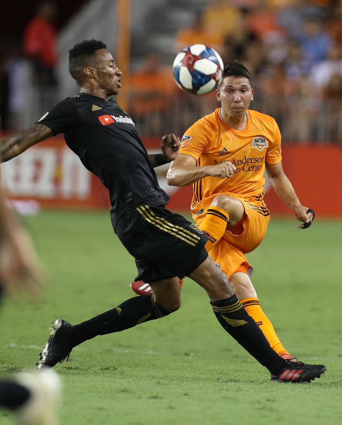 Los Angeles FC midfielder Mark-Anthony Kaye (14) attempts to stop a kick by Houston Dynamo midfielder Tomas Martinez (10) during the first half of an MLS soccer match Friday, July 12, 2019, in Houston.
