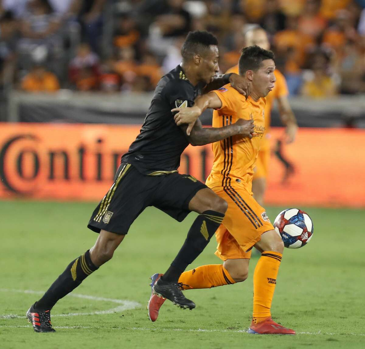 Los Angeles FC midfielder Mark-Anthony Kaye (14) and Houston Dynamo midfielder Tomas Martinez (10) battle for the ball during the first half of an MLS soccer match Friday, July 12, 2019, in Houston.