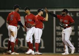Boston Red Sox's Xander Bogaerts, Mookie Betts, Brock Holt and Jackie Bradley Jr., from left, celebrate the team's 8-1 victory over the Los Angeles Dodgers in a baseball game at Fenway Park, Friday, July 12, 2019, in Boston. (AP Photo/Elise Amendola)