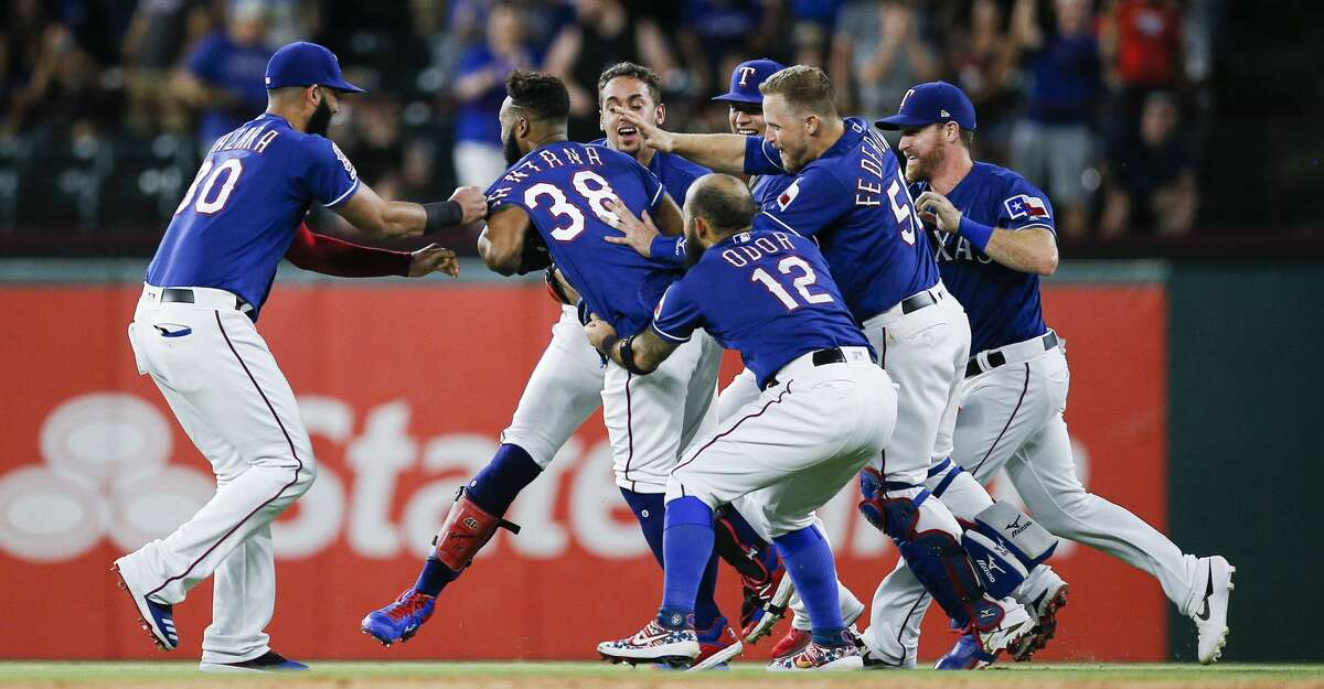 Texas Rangers' Danny Santana (38) is congratulated by teammates after hitting a walkoff single to end a baseball game against the Houston Astros, Friday, July 12, 2019, in Arlington, Texas. (AP Photo/Brandon Wade)