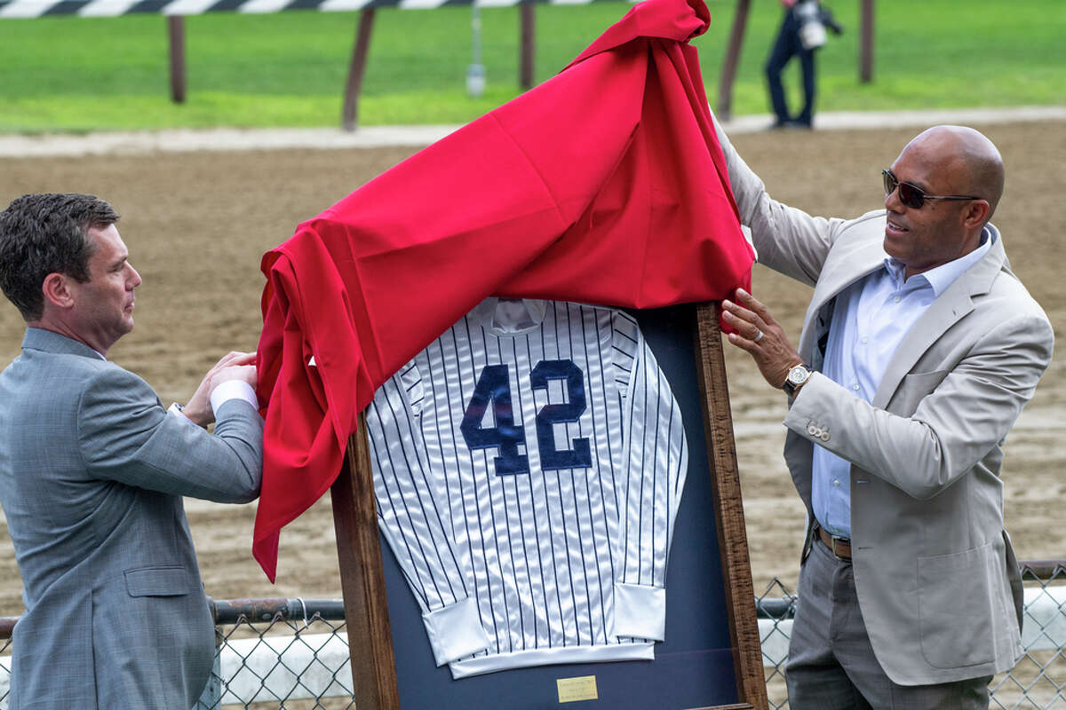 Mariano Rivera, right, is assisted by NYRA CEO David O?•Rourke in the unveiling of racing silks personalized with the number 42 after the third race,